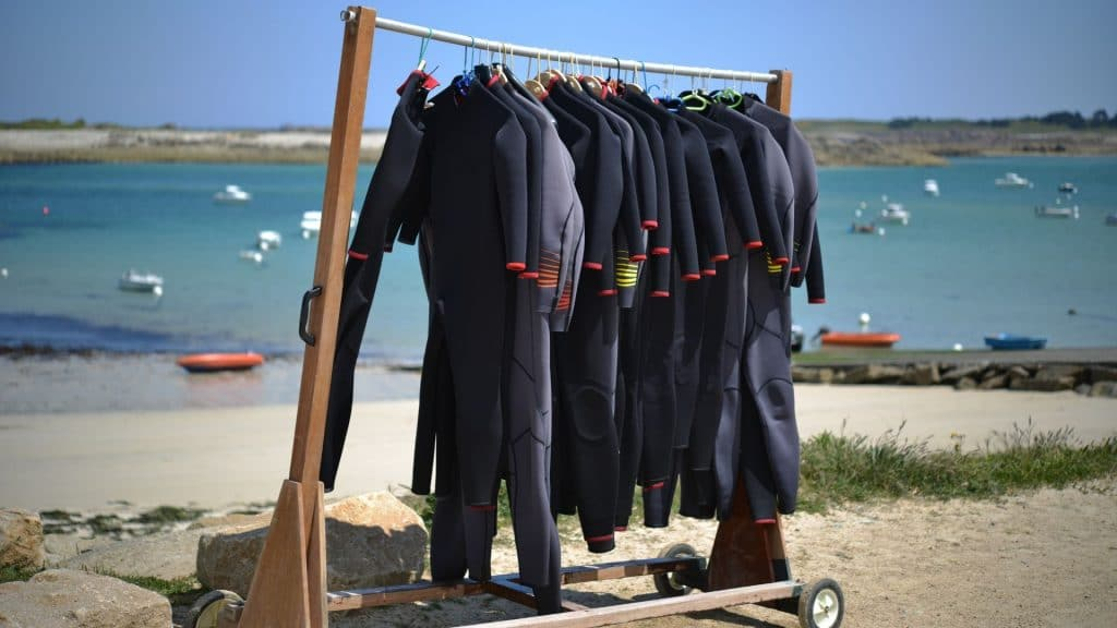 stock image showing a rack of wetsuits on a drying rack by the ocean